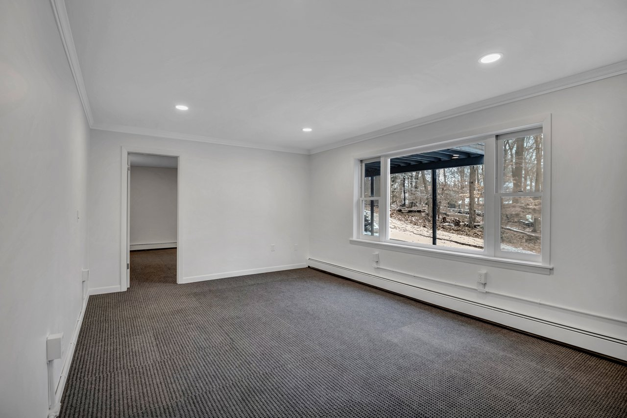 Lower level living space with picture window overlooking the backyard.