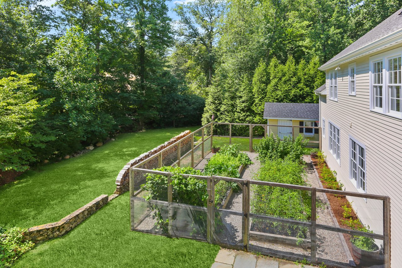 This beautiful home is surrounded by traditional Connecticut stone walls, lovely mature plantings, perfectly designed raised vegetable garden beds, and two bonus sheds.