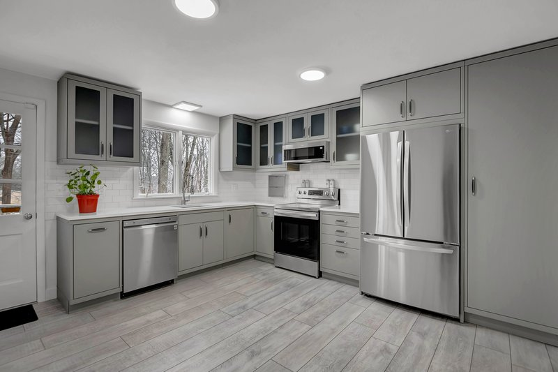 The industrial look of the powder-coated metal cabinets is softened by the elegant quartz countertops and subway tiling.
