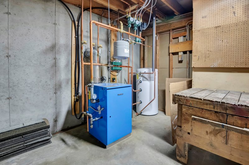 Utility room with new furnace and hot water heater with plenty of room for a workspace.