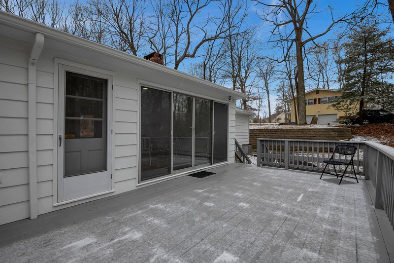 Spacious back deck with sliders to the dining area and door to kitchen.