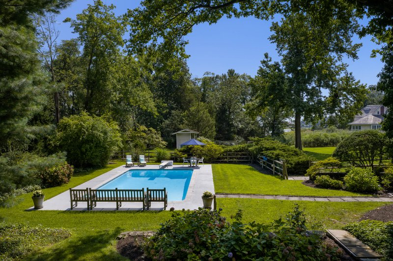 The inground pool is perfectly positioned, offering views of the beautiful sweeping grounds.