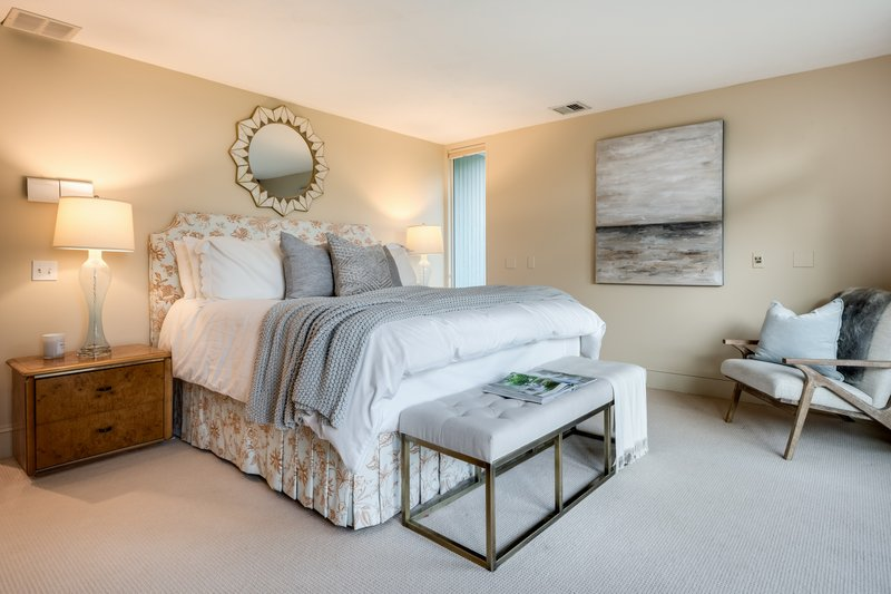 The Master Bedroom, abounding in natural light, offers ample closet space, a dressing area, and sliders that lead to a private balcony.