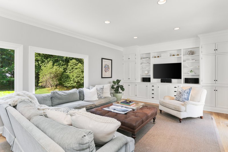 The Family Room is complete with a media station, built-in banquets, and panoramic views of the yard.