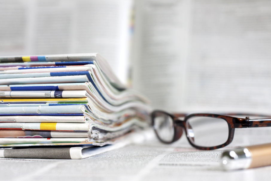 Newspapers and magazines blurred background concept with glasses