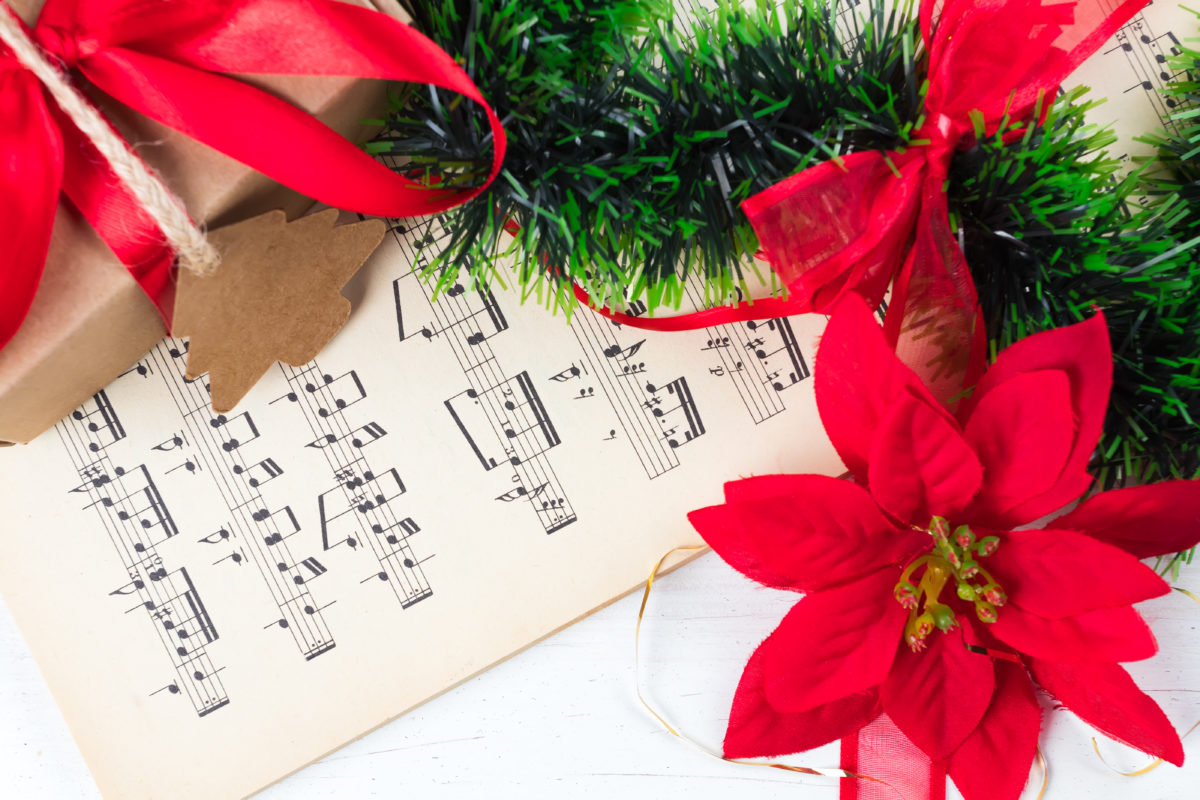 Christmas ornament and music sheet on white natural wooden table. Red ribbon bow. Poinsettia. Gift or present with label and twine.