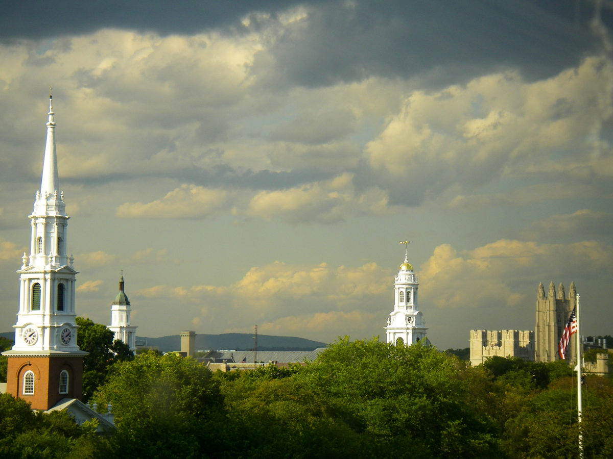 Skyline showing church steeples on the New Haven Green and Storm Clouds arising as well as an american flag and towers of Yale University showing in New Haven Connecticut