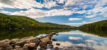 mountain lake with rock jetty and forest in New England