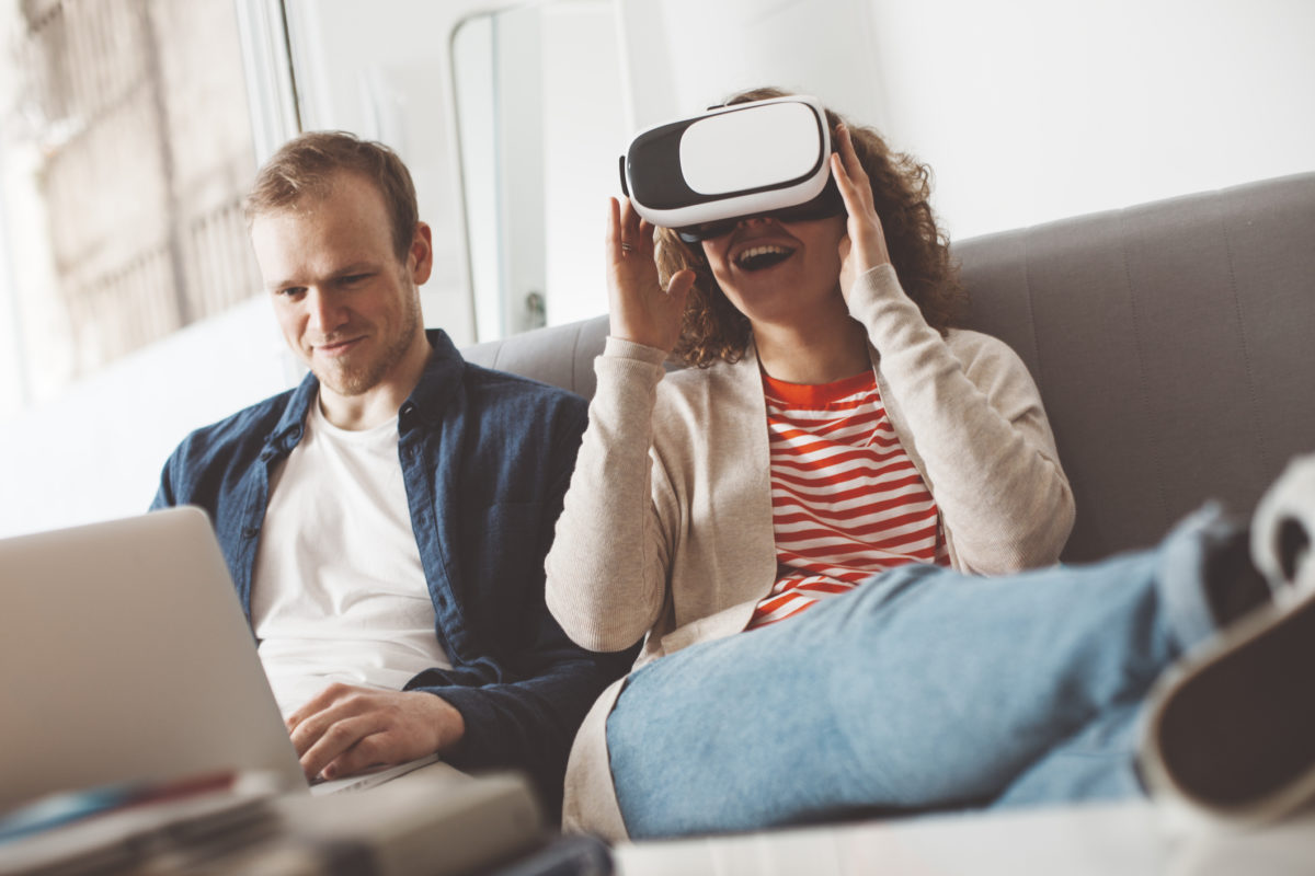 Young couple using electronic devices. Woman watching breathtaking computer game with VR headset. Man typing on laptop. Happy family life