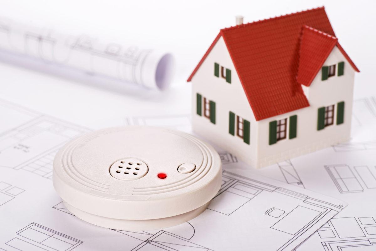 Rauchmelder mit Haus und Bauplänen