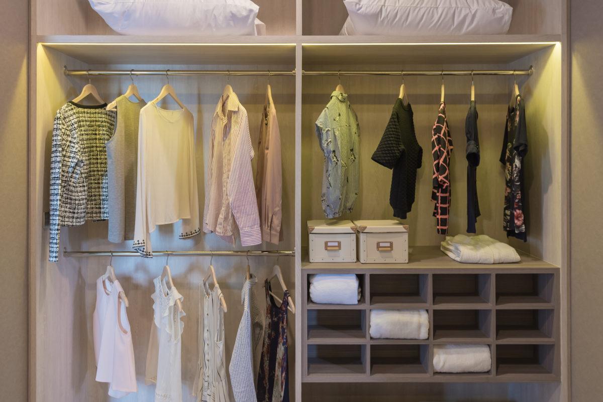 modern closet with clothes hanging on rail, wooden wardrobe, walk in closet interior design