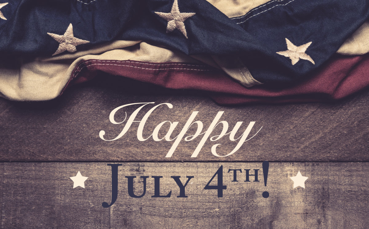 A vintage American flag or bunting on a wooden background with July 4th greeting