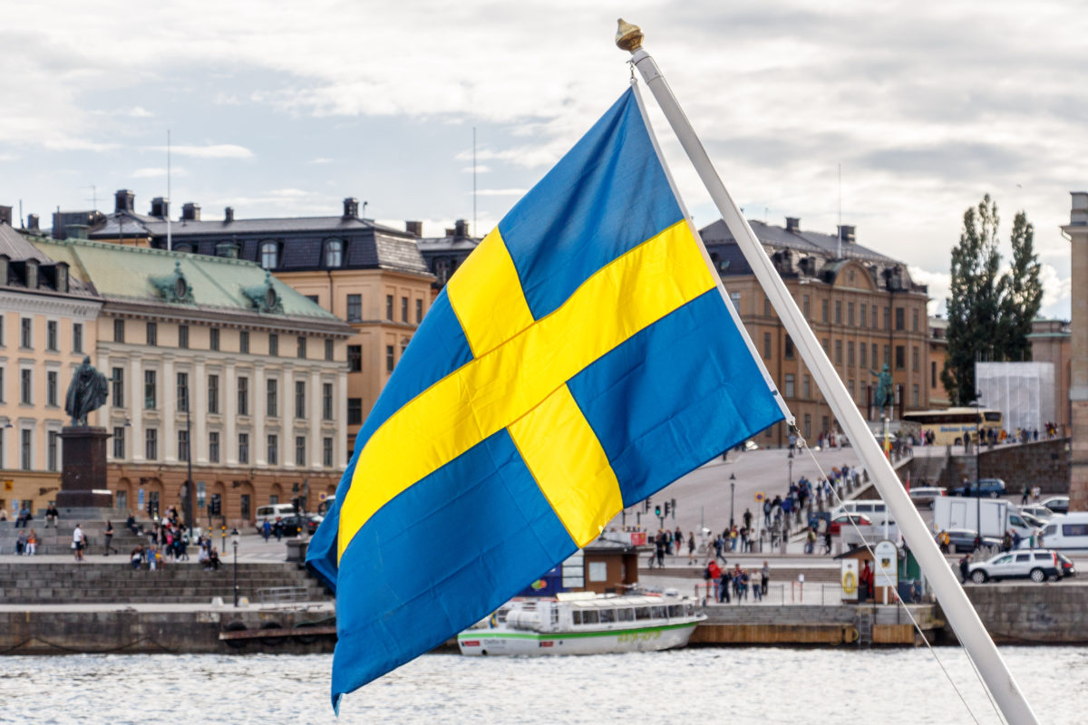 Sweden flag and Stockholm old town Gamla Stan in background