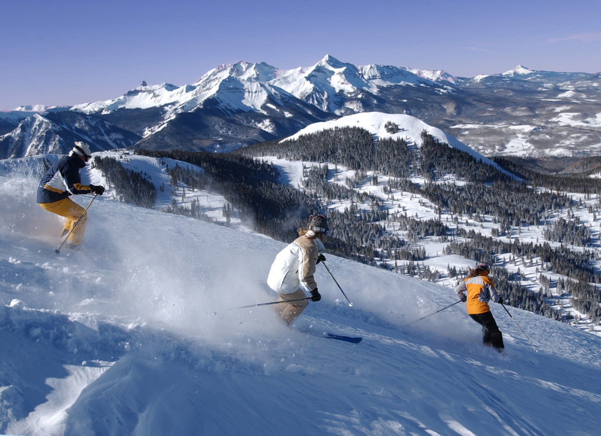 Skiers on Telluride's Gold Hill with the majestic Wilson Massif in the background