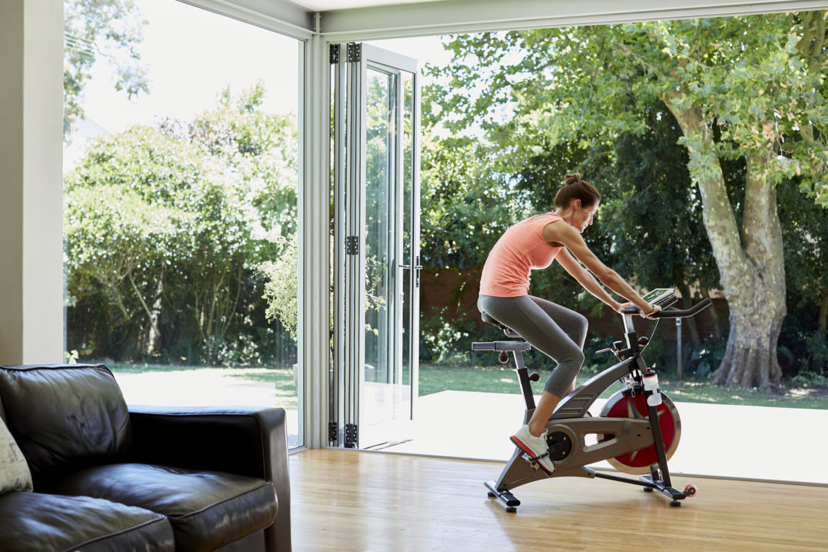 Full length of woman working out on exercise bike at home