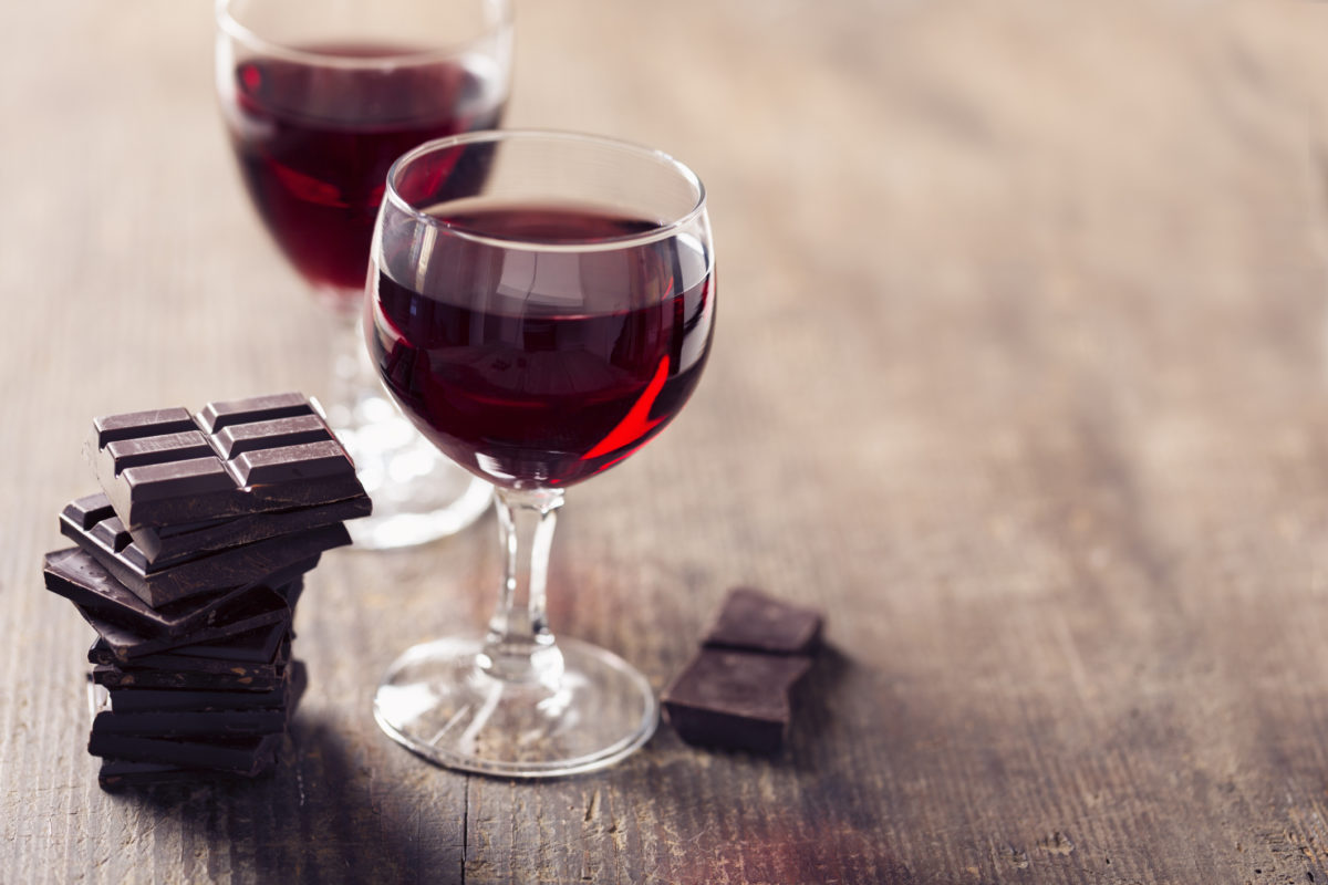 2 glaases with red wine and dark chocolate on wooden background, a wonderful combination
