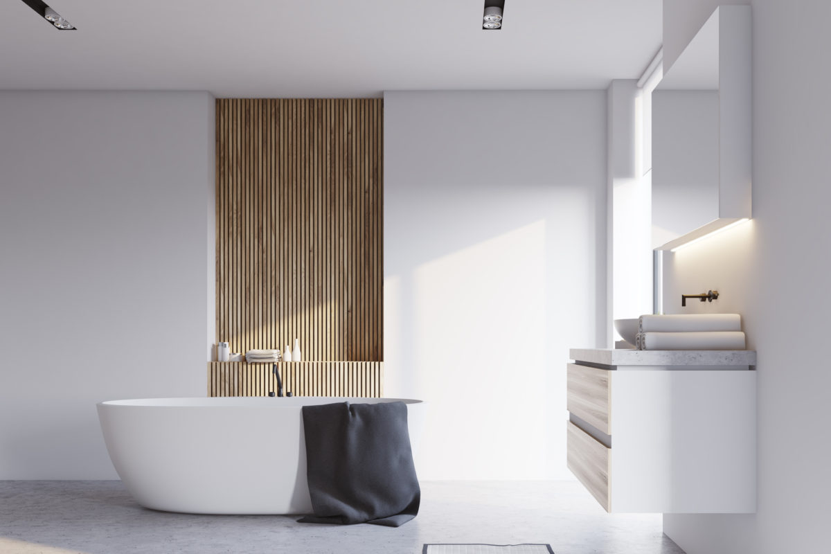 White and wooden bathroom interior with a concrete floor, a white bathtub and a sink with a big mirror hanging above it. 3d rendering mock up