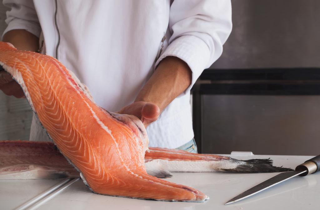 Chef's hand holding fresh piece of salmon