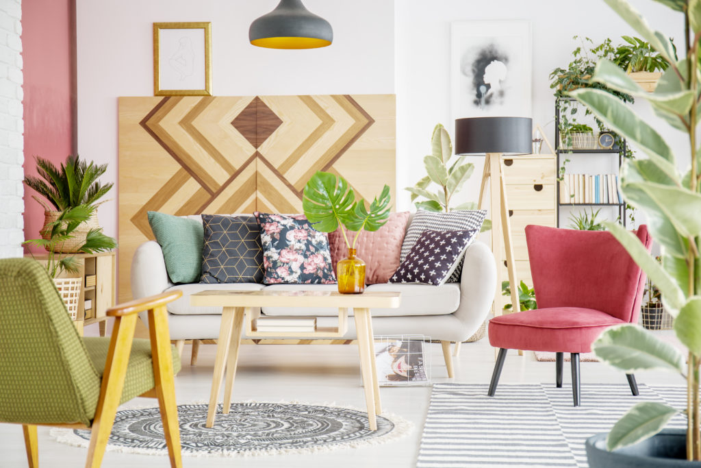 Patterned pillows on sofa next to red armchair in cozy living room interior with wooden furniture