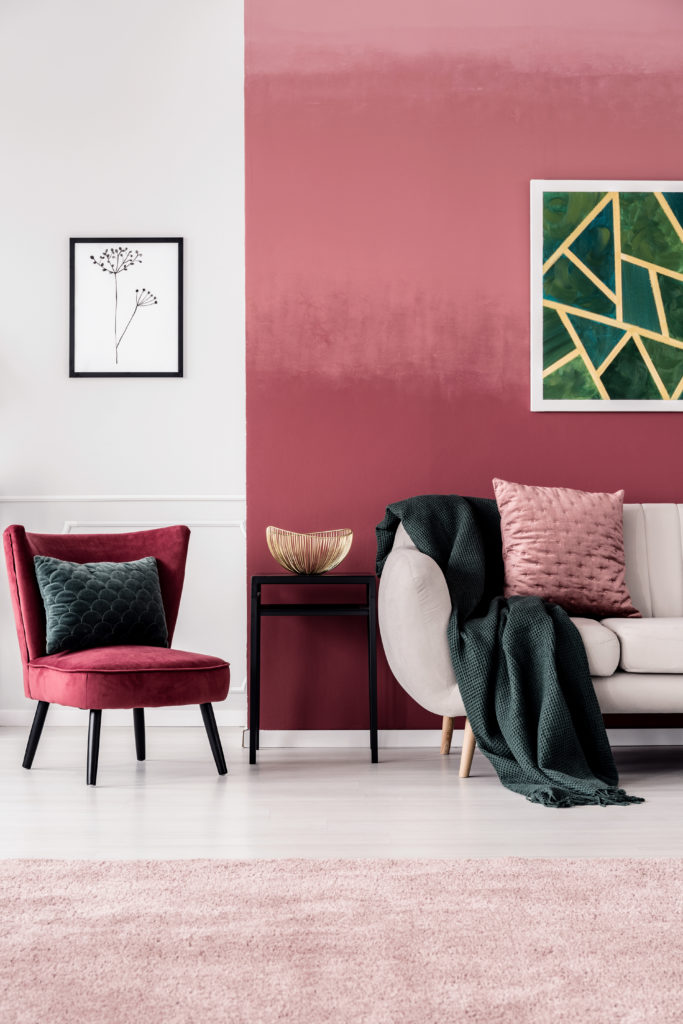 Feminine living room interior with burgundy armchair and dark green blanket on a beige sofa standing against an ombre wall